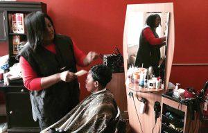 Photo by Max Miller - Opinion Editor Stefanie Williams, owner of Stefanie's Design Studio, cuts customer Deborah Williams' hair.