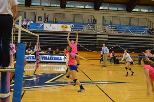 Katie Davis, a junior, jumps for the ball during the Dig Pink game at the Justice Center.  Photo by Max Carter